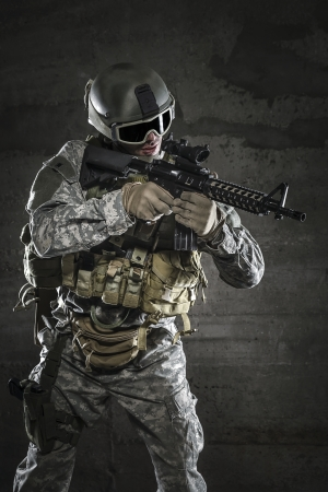 military training: Soldier with mask aiming a rifle