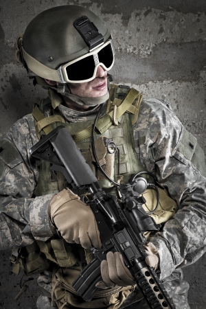 Soldier with rifle and mask on dark background photo