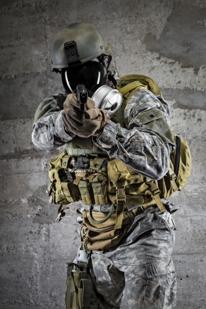 bulletproof vest: Gas Mask Soldier aiming pistol Stock Photo