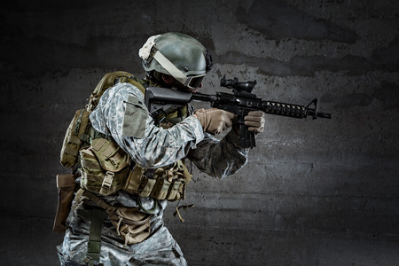 Soldier with mask aiming a rifle photo