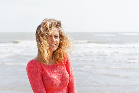 Smiling wind hair girl on the seaside photo