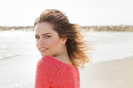 Beautiful green eyes woman smiling on a windy day at the seaside photo