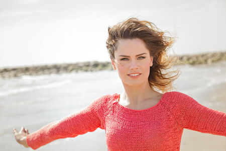 Beautiful young woman smiling on a windy day at the seaside photo