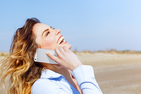 Happy woman laughing on the mobile phone on the seaside photo