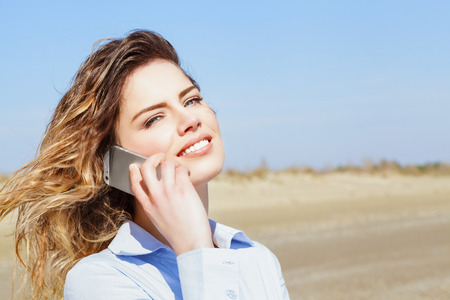 Beautiful woman smiling on the mobile phone and looking at camera photo