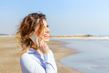 Smiling young woman talking on the mobile phone at the seaside photo