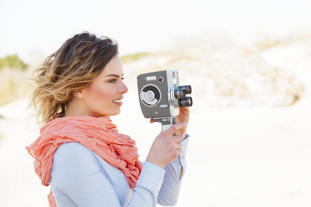 Outdoor Portrait of young woman holding vintage 8mm camera photo