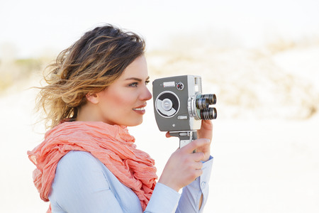 Outdoor Portrait of beautiful woman holding vintage 8mm camera photo