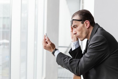 eyesight: Poor eyesight Businessman trying to watch his phone display
