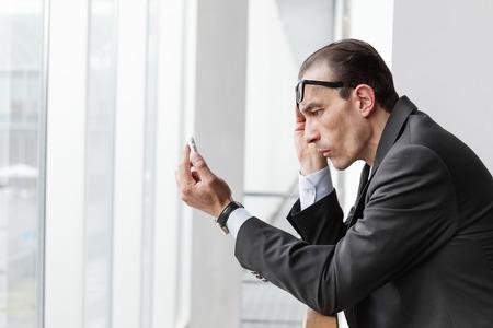 poor eyesight: Poor eyesight Businessman trying to watch his phone display