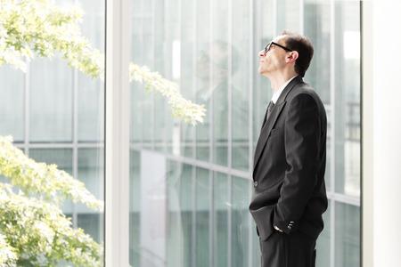 look through window: Portrait of Eyeglasses Daydreaming Businessman looking through the window
