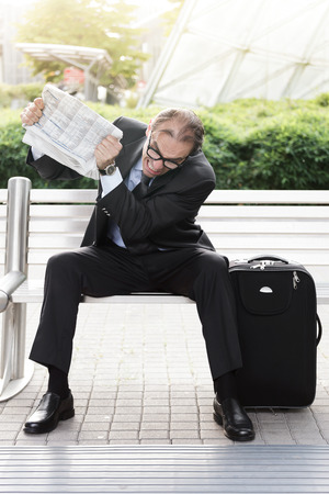 woe: Portrait of Angry businessman with newspaper in his hands  Stock Photo