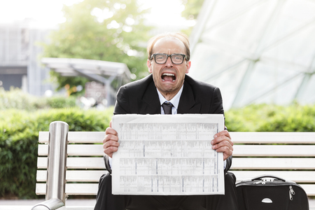 woe: Portrait of screaming businessman with newspaper in his hands