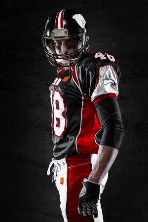 uniforme de futbol: Vista lateral del jugador de f�tbol americano en el fondo oscuro