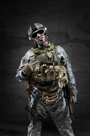 offensive: American Soldier in victory gesture on dark background Stock Photo