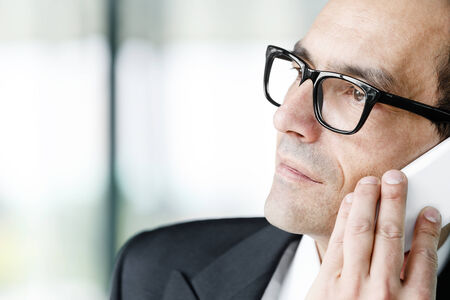 yearning: Portrait of Daydreaming Adult businessman talking on phone