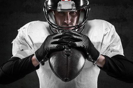 observant: Portrait of american football player on dark background