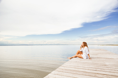 Portrait of smiling Young woman talking on the phone on a pier photo