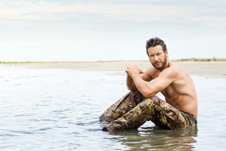 Portrait of Muscle man during fitness training on the water ocean Stock Photo