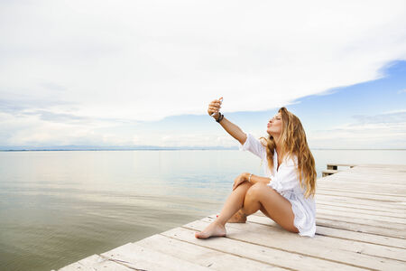 Portrait of beautiful young woman sitting on a pier and taking a self portrait with her smart phone photo