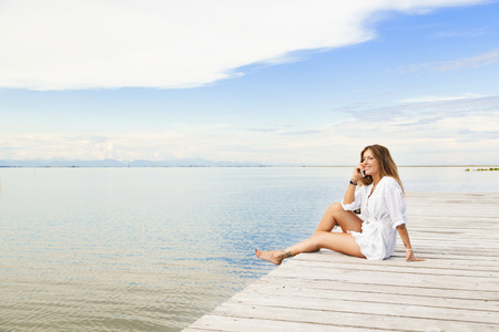 Portrait of Smiling beautiful young woman sitting on a pier and talking on the mobile phone