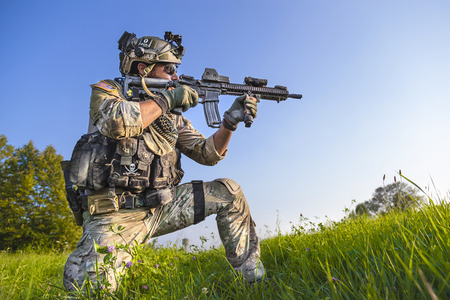 Portrait of American Soldier aiming his rifle on blue sky background