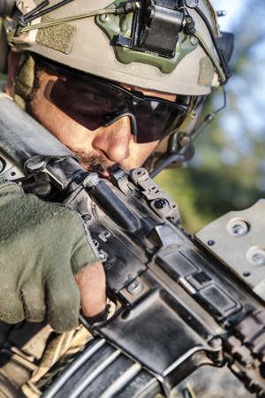 Close up of American Soldier aiming his rifle photo