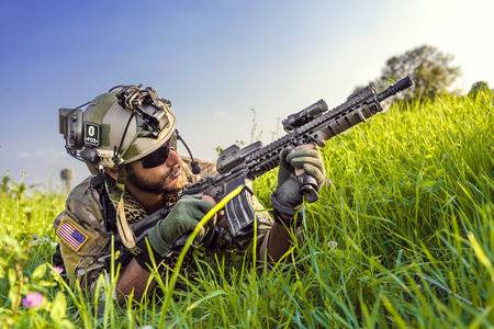 Portrait of American Soldier aiming his rifle on blue sky background photo