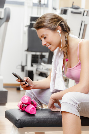 Smiling woman resting from workout at the gym with smartphone photo