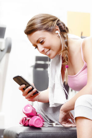 Smiling woman using smart phone with earphones at the gym photo