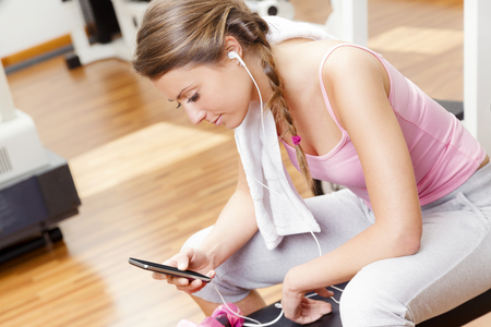 Smiling beautiful woman with smart phone resting from workout at the gym photo