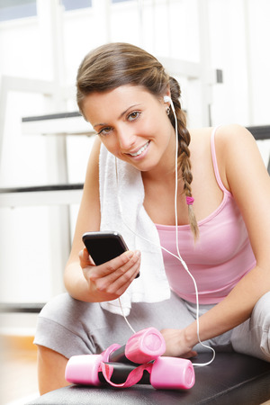 women s legs: Smiling woman listening to music with smart phone at the gym Stock Photo