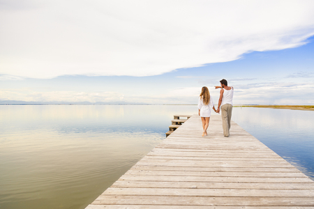 back to back couple: Back view of man and woman couple walking and pointing to the horizon under a blue cloudy sky