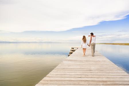 jovenes enamorados: Volver la vista de hombre y mujer pareja caminando y se�alando el horizonte bajo un cielo nublado azul Foto de archivo