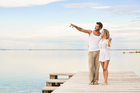 man and woman couple walking and pointing to the horizon under a blue cloudy sky