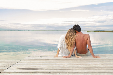 Back view of a man and woman couple sitting on a Jetty under a blue cloudy sky