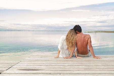 mujeres sentadas: Vista trasera de una pareja hombre y mujer sentada en un embarcadero bajo un cielo nublado azul
