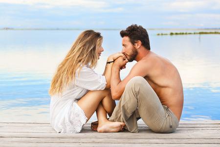 besos hombres: Pareja romántica sentado en un muelle bajo un cielo azul en una puesta de sol Foto de archivo