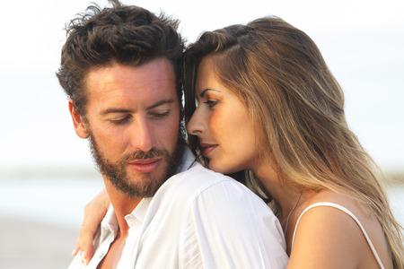 femme romantique: Portrait d'une femme embrassant son homme par derrière sur fond balnéaire Banque d'images