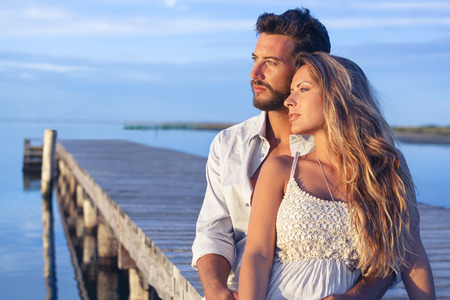 Portrait of a man embracing his woman from behind on seaside background under a blue sky