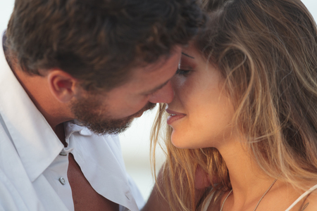 beach kiss: Portrait of a young blonde woman kissing a man Stock Photo