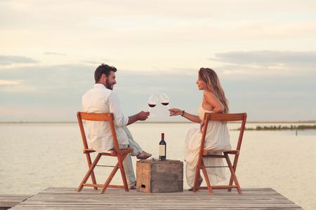 jovenes enamorados: Mujer y hombre pareja beber vino tinto en la playa en un embarcadero Foto de archivo