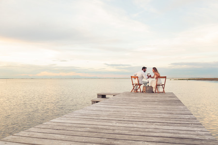 peoples: Woman and man couple drinking red wine at the seaside on a jetty Stock Photo