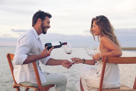 해변에서 레드 와인을 마시는 여자와 남자 커플