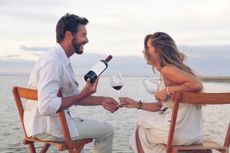 Happy Woman and man couple drinking red wine at the seaside