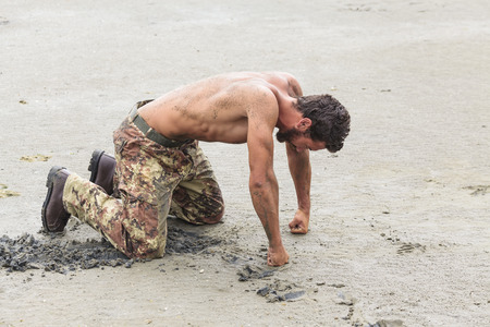 Muscled Shirtless Soldier in Camouflage Pants and Black Shoes Kneeling on the Beach Sand with Fists on the Ground photo
