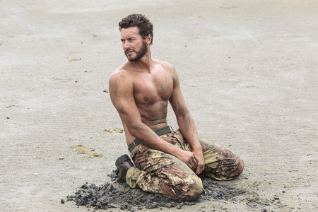 kneeling man: Muscled Shirtless Soldier in Camouflage Pants and Black Shoes Kneeling on the Beach Sand