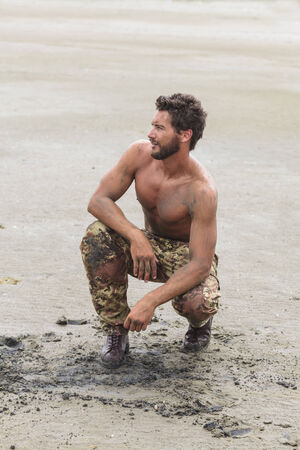 inscrutable: Muscled Shirtless Soldier in Camouflage Pants and Black Shoes on the Beach Sand