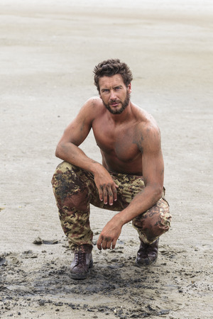 shirtless guy: Muscled Shirtless Soldier in Camouflage Pants and Black Shoes on the Beach Sand