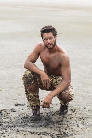 en cuclillas: Soldado Sin camisa musculoso con pantalones de camuflaje y zapatos negros en la arena de la playa